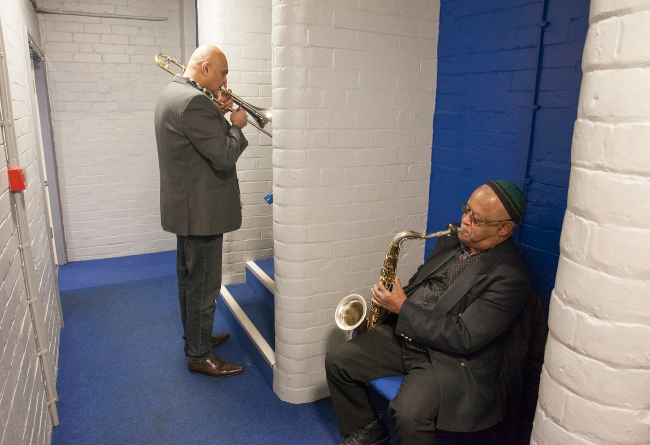 The horn section of Jools Holland's Rhythm and Blues Orchestra warm up backstage